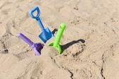 Niebieski, zielony i fioletowy plaży łopata tkwi w piasku na słonecznym — Zdjęcie stockowe