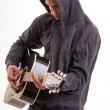 Постер, плакат: Young man dressed in hoodie try to understand how to play acous