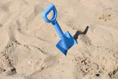 Blue beach shovel stuck in the sand by a child — Stok fotoğraf
