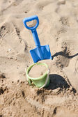 A beach bucket and a beach shovel stuck in the sand by a child — Stockfoto