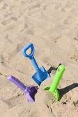 Blue, green and purple beach shovel stuck in the sand on a sunny — Foto de Stock