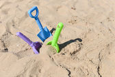 Blue, green and purple beach shovel stuck in the sand on a sunny — Stok fotoğraf