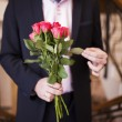 Young min suit with roses in their hands — Stock Photo #26087357