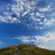 Stock Photo: Grassy hill to the road and the sky