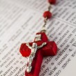 Red color cross with red chaine of beads on Bible's page - Stock Photo