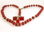 Red color cross with red chaine of beads like heart — Stock Photo