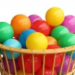 Colour plastic balls in basket over white background — Stock Photo #30911997