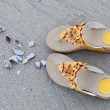 A design of shoes and seashell on the sand beach — Stock Photo