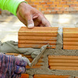 Worker create a brick wall with trowel and cement mortar — Stock Photo