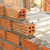 Red brick wall creating with cement mortar — Stock Photo