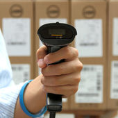 Hoding barcode scanner over the boxes background — Stok fotoğraf