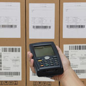 Scanning boxes with barcode scanner operated on smartphone — Stock Photo