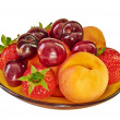 图库照片: Plate with fruits macro isolated on white.