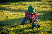 A Young Farmer Boy Pushes a Toy Tractor Outside — Stock Photo