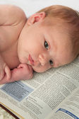 Baby Lies on Scripture of Dedication — Stock Photo