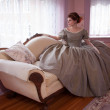 Historically Clad Woman Sitting on Couch and Looking out Window — Stockfoto