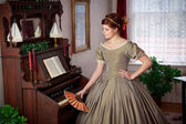 Historically Clad Woman Standing by a Pump Organ — Stock Photo