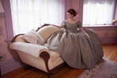 Historically Clad Woman Sitting on Couch and Looking out Window — Stock Photo