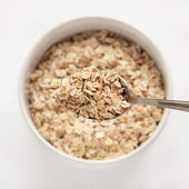 Oat flakes in bowl and spoon — Stock Photo