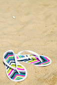 A pair of flip-flops on the sand of a beach — Stock Photo