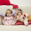 Two little girls sitting on the couch — Stock Photo #22511637