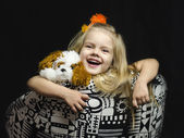 A little girl with a soft toy in the chair. — Stock Photo