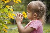 Three-year girl sniffing yellow flower — Stock Photo