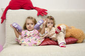 Two little girls sitting on the couch — Stock Photo