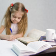 Girl leafing through the book and wrote on a sheet of paper abstract sitting at the table — Stockfoto
