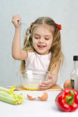 Girl playing in a cook churn whisk the eggs in a glass bowl — Stock Photo
