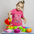 Girl pours a Cup of water from the teapot playing child kitchen utensils — Stock Photo