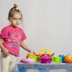 Girl plays child kitchen utensils — Stock Photo
