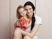 A happy mother and daughter at home cuddling and watching the frame — Stock Photo