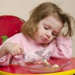 Stock Photo: Two-year-old girl eats with fork at table in kitchen