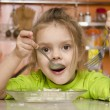 A four year old girl eats with a fork and spoon sitting at the table in the kitchen — ストック写真