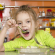 A four year old girl eats with a fork and spoon sitting at the table in the kitchen — Stockfoto