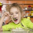 Four year old girl eats with fork and spoon sitting at table in kitchen — Zdjęcie stockowe #24406637