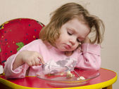Two-year-old girl eats with a fork at the table in the kitchen — Stock Photo