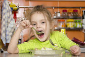 A four year old girl eats with a fork and spoon sitting at the table in the kitchen — Стоковое фото