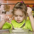 A four year old girl eats with a fork — Стоковая фотография