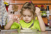 A four year old girl eats with a fork — Стоковое фото