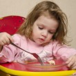 Two-year-old girl eats sitting at the table in the kitchen. — Stock Photo #24508197