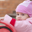 Stock Photo: Two-year-old girl thoughtfully looks sitting on bike