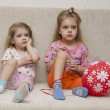 Two little girls sitting on the couch with a ball — Stock Photo