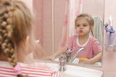 Four-year-old girl rinse teeth after cleaning in the bathroom — Stock Photo