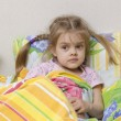 Four-year-old girl with pigtails lying in bed under the blanket — Stock Photo
