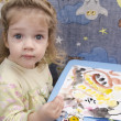 Stock Photo: Two-year-old girl is painting at table and looks in frame