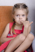 Girl sitting on the couch and thoughtfully looks to the left — Stock Photo