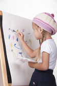The girl in the image of the artist draws on the easel — Stock Photo