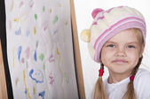 Portrait of a girl in the image of the artist, near the drawn her picture — Stock Photo